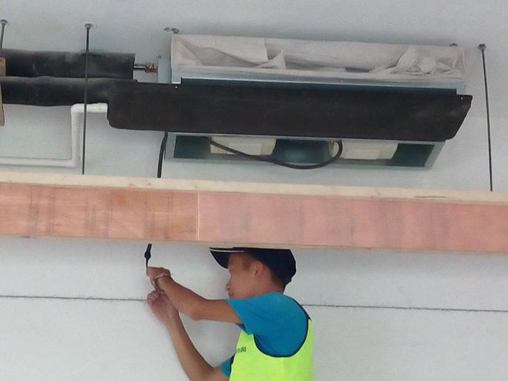 舒适100网工程服务人员正在检查风机盘管线路