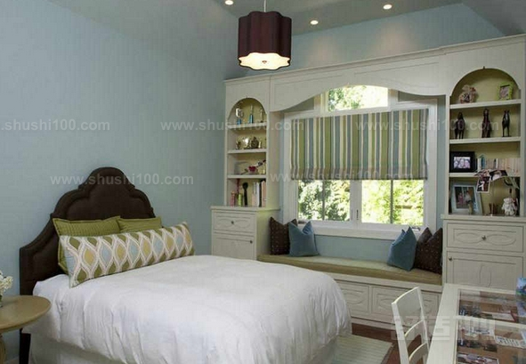 卧室窗台两边书柜示例二   简约素雅风格卧室规划的很不错,浅蓝色的墙壁粉刷,带来了清新自然的元素,独立的小飘窗很明朗大方,舒适的坐垫和靠背在这里环绕,为生活增添了便捷,在这里休息,感受惬意轻松的生活定是极好的。两侧展示柜摆置,对称式的设计很不错,可以存放一些简单的生活物件,充盈了整个卧室。  卧室窗台两边如何利用卧室窗台两边书柜示例三