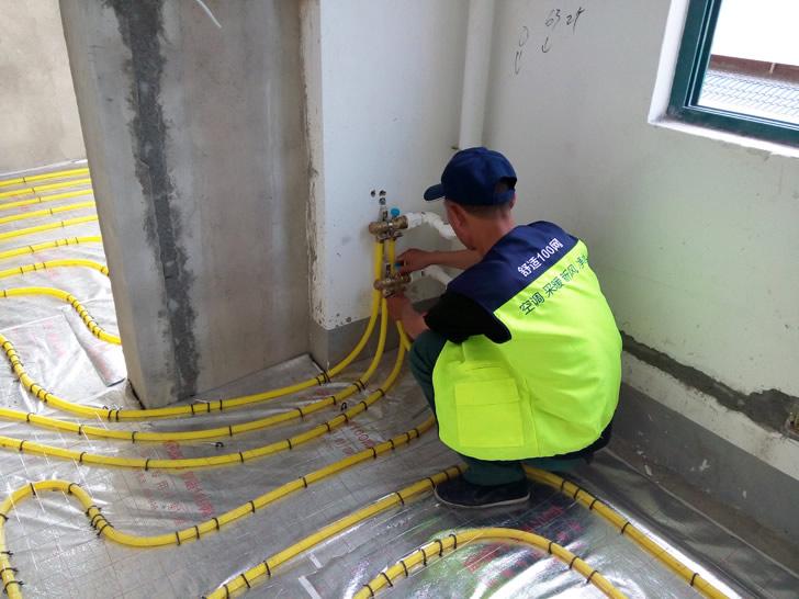 舒适100网工程服务人员正在安装地暖分集水器
